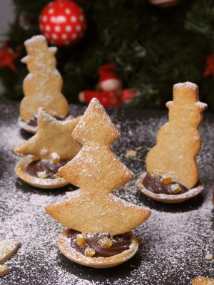 Sablés de Noël à l'orange et à la canelle, garnis d'une délicieuse ganache au chocolat.